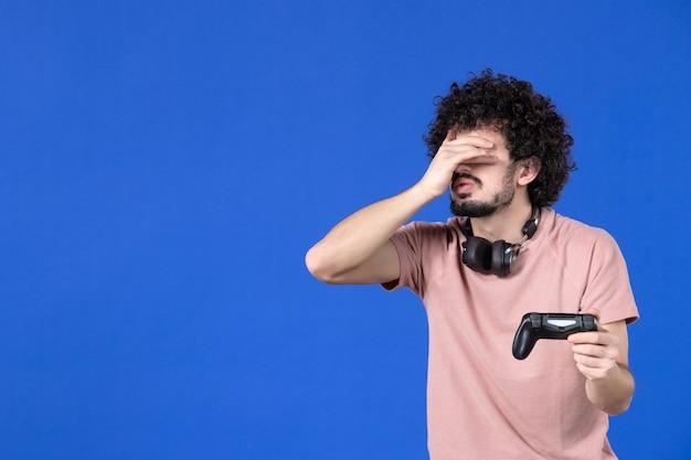 Вид спереди мужчина-геймер играет в видеоигру с геймпадом синий фон футбол взрослый радость диван молодой победитель подростки виртуальный молодой игрок