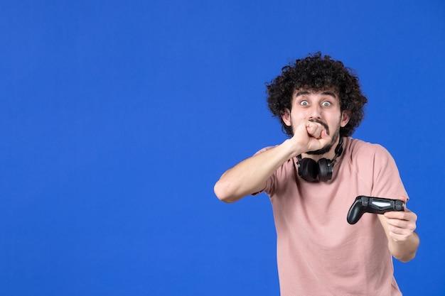 Вид спереди мужчина-геймер играет в видеоигру с геймпадом синий фон подросток футбол взрослый радость диван молодой победитель виртуальный молодежный игрок