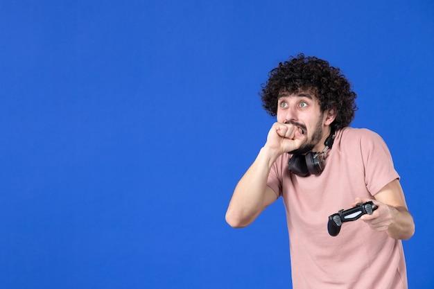 Вид спереди мужчина-геймер играет в видеоигру с геймпадом синий фон подросток футбол взрослый радость диван молодой победитель виртуальная молодежь игроки
