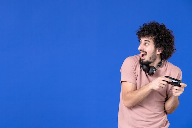 Вид спереди мужчина-геймер играет в видеоигру с геймпадом синий фон молодежь радость футбол диван виртуальный игрок выигрывает взрослый подросток