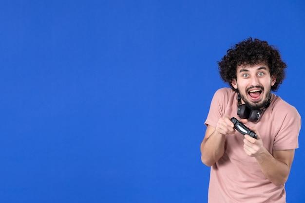 Вид спереди мужчина-геймер играет в видеоигру с геймпадом синий фон молодежь радость подросток футбол диван виртуальные игроки выигрывающий взрослый