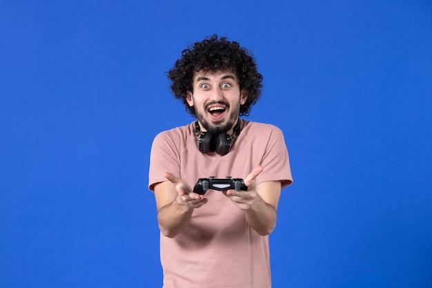 Вид спереди мужчина-геймер играет в видеоигру с геймпадом на синем фоне виртуальный взрослый видео радость игрок футбол подросток выигрывает