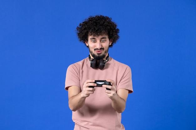 Вид спереди мужчина-геймер играет в видеоигру с геймпадом на синем фоне виртуальный взрослый видео радость игроки молодой футбол подросток выигрывает