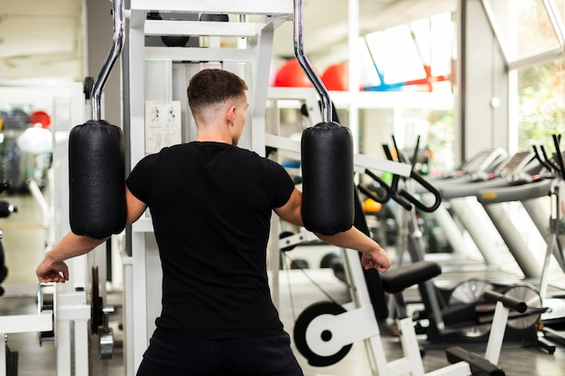 Front view male at gym doing arms exercise