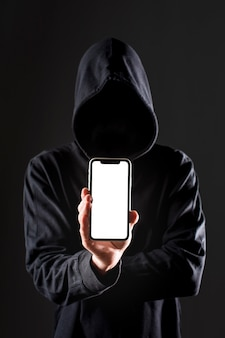 Front view of male hacker holding smartphone