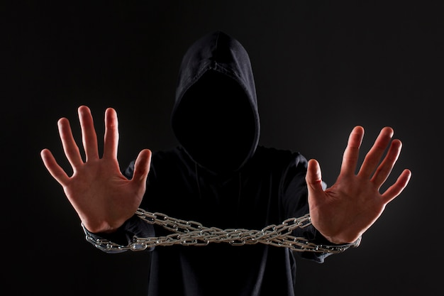Front view of male hacker with metal chain around hands