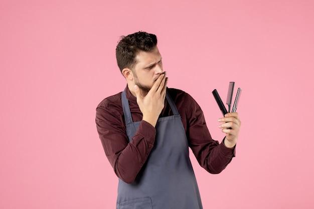 Vista frontale parrucchiere maschio che tiene spazzole per capelli su sfondo rosa