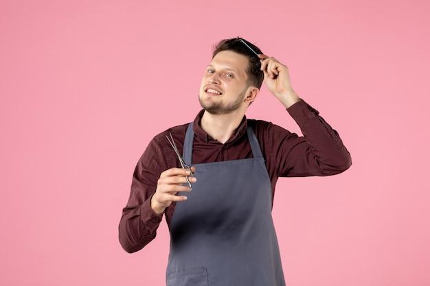 ピンクの背景に彼の髪の世話をするヘアブラシとはさみを持つ正面図の男性美容師