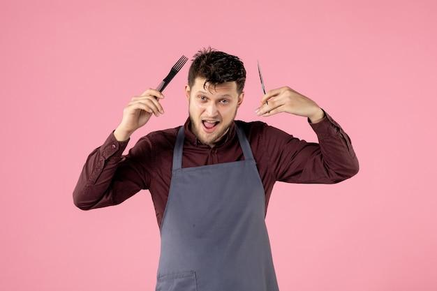 Parrucchiere maschio vista frontale con spazzola per capelli e forbici su sfondo rosa