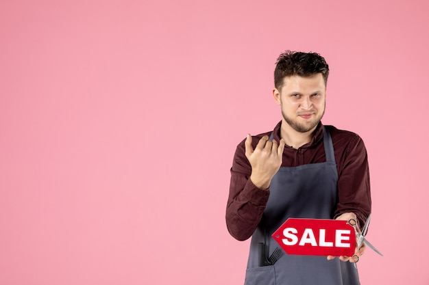 Front view male hairdresser with red sale nameplate on pink background