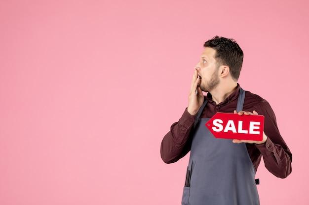 Мужской парикмахер вид спереди с табличкой продажи и ножницами на розовом фоне