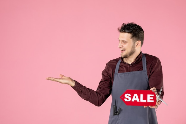ピンクの背景に販売ネームプレートと正面の男性美容師