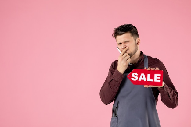 Front view male hairdresser with sale nameplate and scissors on pink background