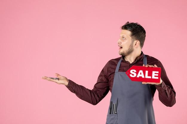 Parrucchiere maschio vista frontale con targhetta di vendita e forbici su sfondo rosa