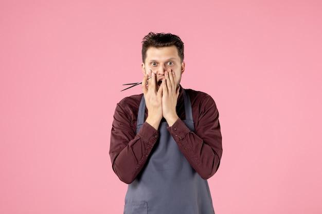 분홍색 배경에 가위가 있는 전면 보기 남성 미용사