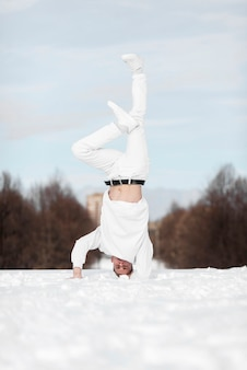 Front view of male hip hop performer standing on head in the snow