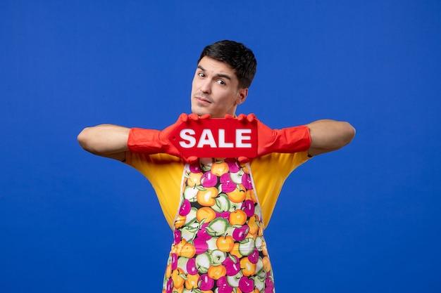 Governante maschio di vista frontale in grembiule che sostiene il segno di vendita sullo spazio isolato blu