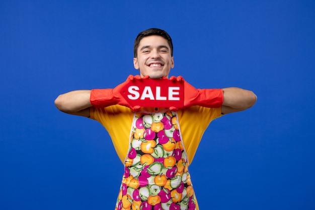 Governante maschio di vista frontale in grembiule che sostiene il segno di vendita su spazio blu