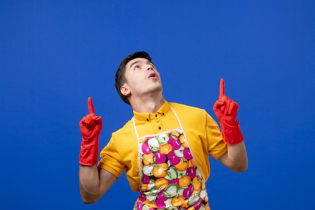 Front view male housekeeper in apron pointing with finger up
