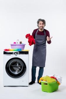 白い壁の洗濯機の近くに立っている赤いタオルを保持している正面図男性の家政婦