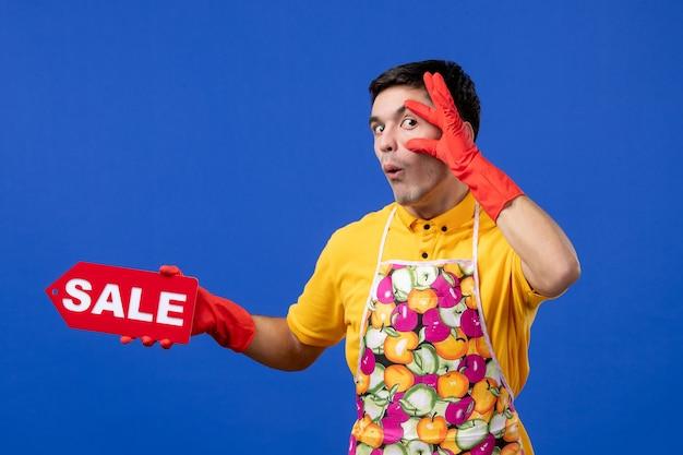 파란색 공간에 눈을 크게 뜨고 판매 표지판을 들고 노란색 티셔츠를 입은 남성 가정부 전면보기