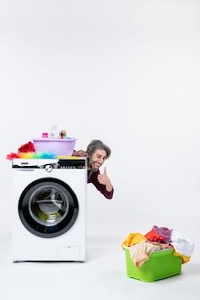 흰색 벽에 세탁기 세탁 바구니 뒤에 앉아 엄지손가락을 위로 만드는 전면 보기 남성 가정부