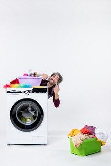 흰색 벽에 세탁기 세탁 바구니 뒤에 앉아 그의 미소를 보여주는 전면보기 남성 가정부