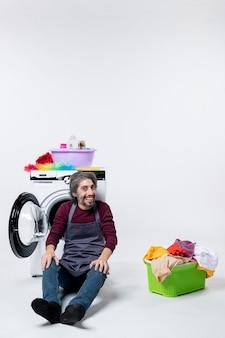 Governante maschio di vista frontale che si siede davanti al cesto della biancheria della lavatrice sulla parete bianca