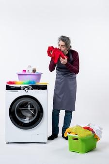 白い壁の洗濯機の近くに立っている赤いタオルの匂いを嗅ぐ正面図男性の家政婦