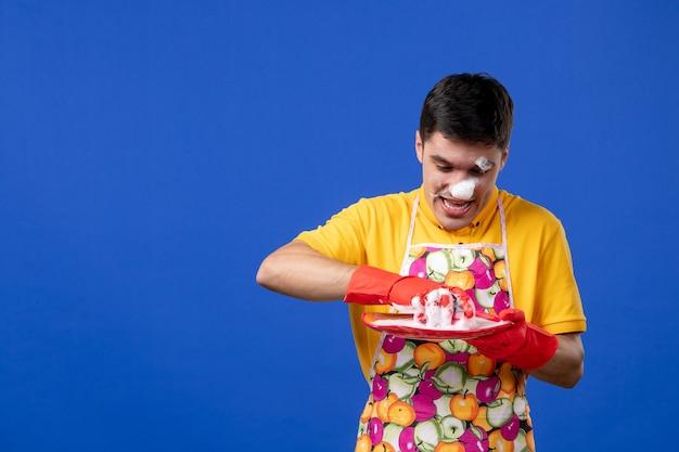 青いスペースの彼の顔の洗浄プレートに泡を持つ正面図の男性の家政婦 無料写真