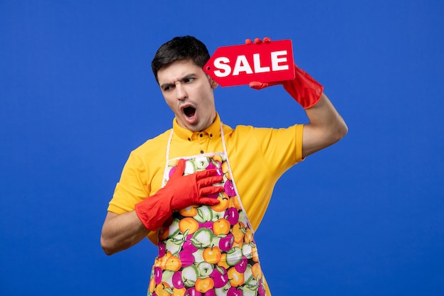 Front view male housekeeper in yellow t-shirt putting sale sign near his head on blue space