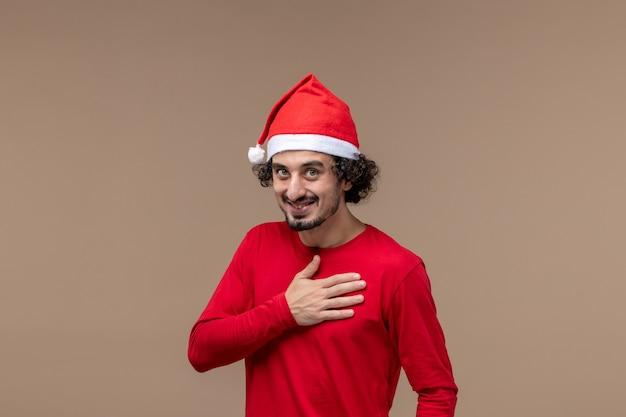 Вид спереди мужчина в красном кланяется и улыбается на коричневом фоне, праздничные эмоции, рождество