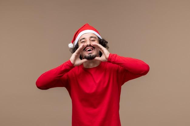Вид спереди мужчина в красном эмоционально зовет на коричневом фоне, праздничные эмоции, рождество