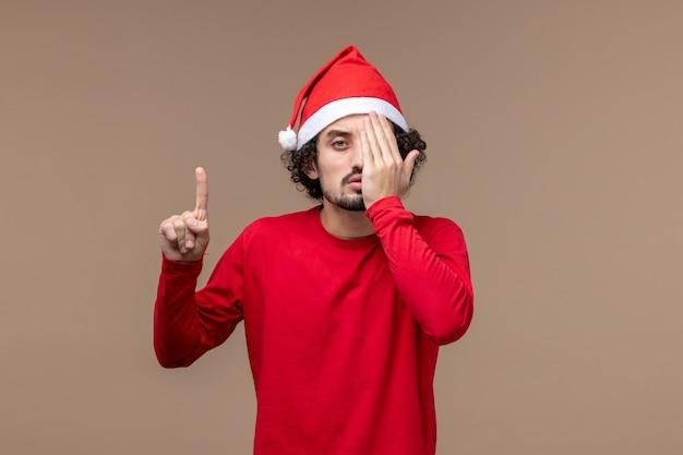 Вид спереди мужчины в красном, закрывающем половину лица на коричневом фоне, праздничные эмоции, рождество