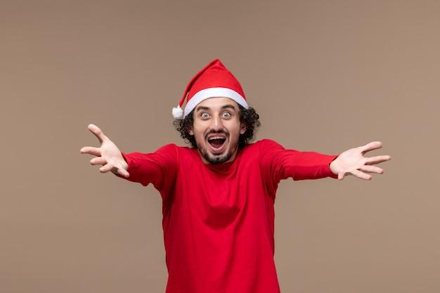 Вид спереди мужчина в красном эмоционально позирует на коричневом фоне праздник эмоции рождество