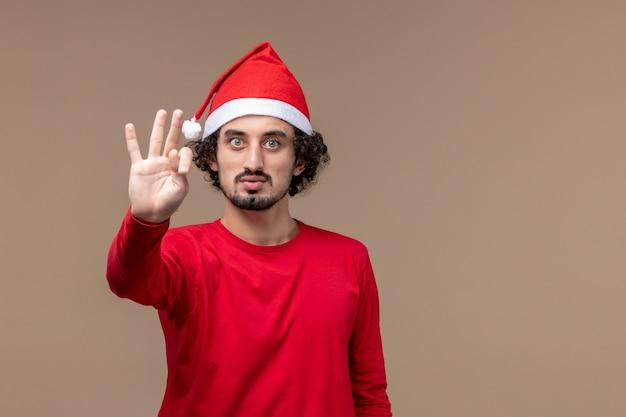 Вид спереди мужчина в красном, показывающий номер на коричневом фоне, праздник эмоции, рождество