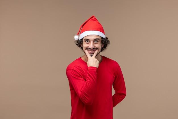 Вид спереди мужчина в красном улыбается на коричневом фоне праздник эмоции рождество