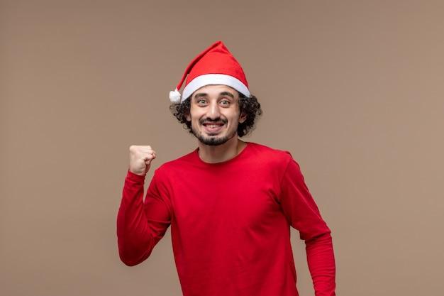 Вид спереди мужчина в красном с возбужденным выражением на коричневом фоне праздничные эмоции рождество