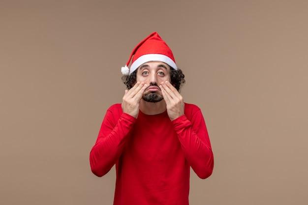 Вид спереди мужчина в красном с грустным лицом на коричневом фоне праздничные эмоции рождество