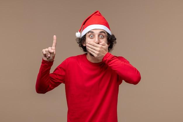 Вид спереди мужчина в красном с шокированным выражением на коричневом фоне праздничные эмоции рождество
