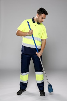 Front view of male janitor with broom