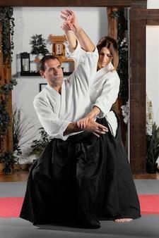 Vista frontale dell'istruttore di arti marziali maschio nella sala pratica con il tirocinante