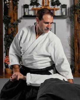 Vista frontale dell'istruttore di arti marziali maschio che pratica con il tirocinante femminile
