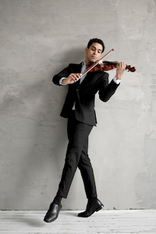 Front view of male musician dancing and playing violin