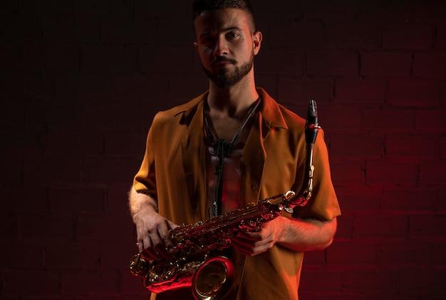 Vista frontale del musicista maschio che tiene un sassofono