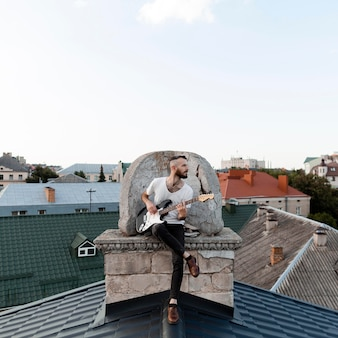 Front view of male musician playing electric guitar on roof top