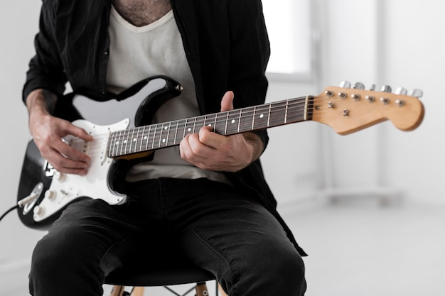 Front view of male musician playing electric guitar