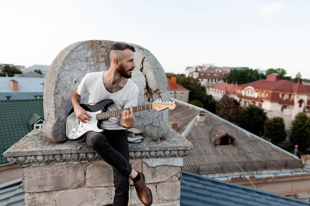 Front view of male musician on roof top playing electric guitar
