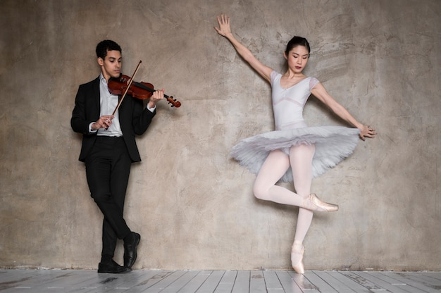 Front view of male musician with violin and ballerina
