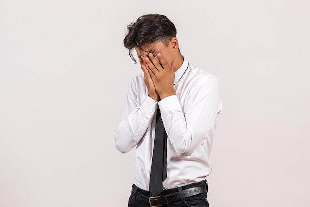 Front view male office worker covering his face on white wall office work job male human